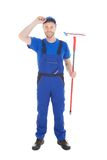 Confident young male cleaner holding mop Royalty Free Stock Photography