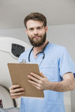 Confident Young Male Doctor With Clipboard In Examination Room. Portrait of confident young male doctor with clipboard standing in examination room Stock Image
