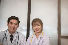 Confident young male & female doctor smiling at camera.  Portrai. T of asian medical staff, physician or practitioner at hospital Royalty Free Stock Images