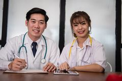 Confident young male & female doctor smiling at camera.  Portrai. T of asian medical staff, physician or practitioner at hospital Stock Images