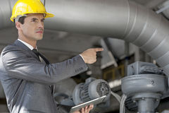Confident young male manager with digital tablet pointing at machinery in industry Royalty Free Stock Images