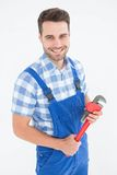 Confident young male repairman holding adjustable pliers Royalty Free Stock Images