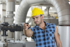 Confident young male worker pointing away in industry Stock Image