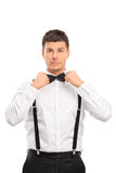 Confident young man adjusting his bow-tie Royalty Free Stock Photos
