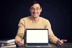 Confident young man advertising laptop Royalty Free Stock Photos