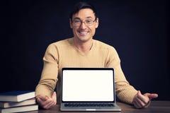 Confident young man advertising laptop Royalty Free Stock Photos