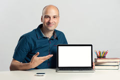 Confident young man advertising laptop Royalty Free Stock Image
