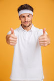 Confident young man athlete showing thumbs up with both hands Royalty Free Stock Photography