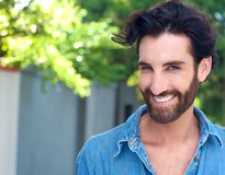Confident young man with beard smiling outdoors Royalty Free Stock Photography