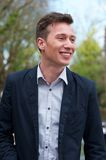 Confident young man in blue jacket, smiling outdoors Royalty Free Stock Image