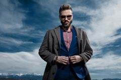 Confident young man closing his jacket`s buttons. And looking to the camera while wearing a gray coat, blue suit and sunglasses, standing on outdoor background royalty free stock photos