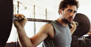 Confident young man exercising with barbell. At fitness center. Male bodybuilder working out with heavy weights at cross training gym stock image