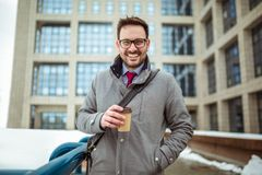 Young man in glasses drinking coffee outdoors. Confident young man in glasses drinking coffee outdoors royalty free stock photography