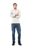 Confident young man in gray long sleeved shirt and jeans with crossed arms. Full body length portrait isolated over white studio background stock photography