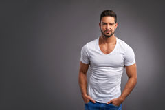 Confident young man. A handsome confident young man standing seriously in a white t-shirtr Stock Photos