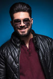 Confident young man with long beard smiling. Confident young man with long beard wearing leather jacket and sunglasses is smiling to the camera Royalty Free Stock Image