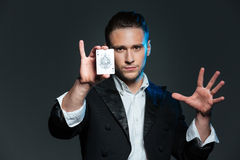 Confident young man magician showing ace card Stock Images
