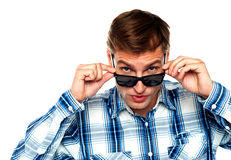 Confident young man peeping from goggles Stock Photo