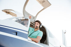 Confident young man pilot in small plane. Portrait of confident young man pilot in small plane royalty free stock photos