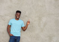 Confident young man pointing and smiling stock images