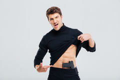 Confident young man posing and poiting on his gun Royalty Free Stock Image
