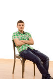 Confident young man sitting comfortably in a chair Stock Photos