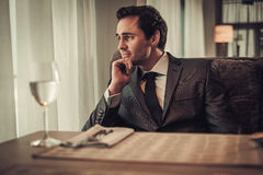 Confident young man sitting in restaurant waiting for somebody. Royalty Free Stock Photo