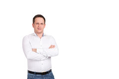 Confident young man in smart casual wear looking at camera and holding arms crossed while standing against white background. Stock Images