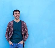 Confident young man smiling against blue background Royalty Free Stock Photography