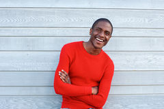 Confident young man smiling with arms crossed Stock Image