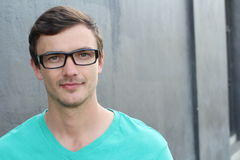Confident young man in spectacles looking at camera and smiling isolated over gray Stock Images