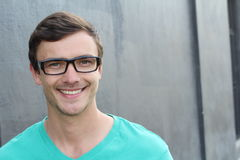 Confident young man in spectacles looking at camera and smiling. Isolated over gray Stock Image