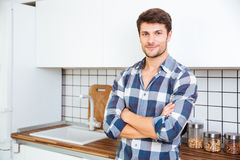 Confident young man standing with arms crossed on the kitchen Stock Photo