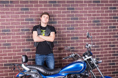 Confident Young Man Standing Behind his Motorbike Stock Photography