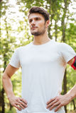 Confident young man standing in forest Stock Image