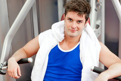 Confident young man with a towel using bench press Stock Photos