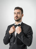 Confident young man in tuxedo with bow tie posing at camera holding suit collar. Royalty Free Stock Photography