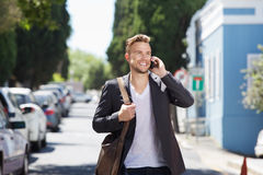 Confident young man walking outside with mobile phone Stock Photo