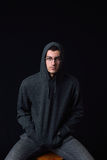 Confident young man wearing glasses and black hoodie posing on a Stock Photos