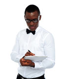 Confident young man writing on notepad Stock Photography