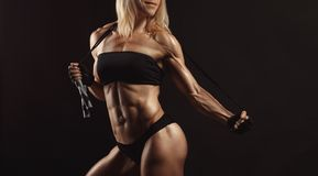 Confident young muscular fitness female. Looking away and posing with jumping rope in the studio on a black background. Front view of woman bodybuilder with Royalty Free Stock Images