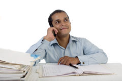 Confident Young office employee at Work and talking on phone while at his desk amidst a pile of files. Stock Image
