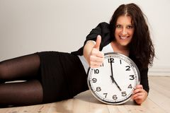 Confident Young Professional with a Clock. Portrait of a young confident professional holding a clock while giving a thumbs up sign Stock Image