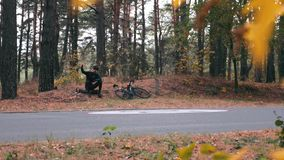 Confident young professional cyclist in black helmet and sunglasses sitting in autumn park and taking selfie or photos on phone. H. Andsome athlete relaxing stock video footage