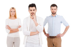 Confident young professionals. Three confident young people in smart casual wear looking at camera while standing against white background Royalty Free Stock Photography