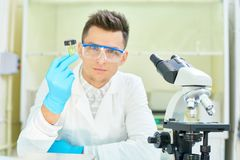 Confident Young Researcher Posing for Photography. Waist-up portrait of confident young researcher wearing safety goggles and white coat sitting at desk of Stock Photography