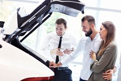 Confident young salesman explaining car features to the young attractive owners. Picture of confident young salesman explaining all the car features to the young stock photo