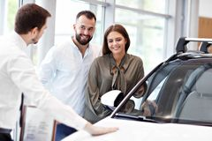 Confident young salesman explaining car features to the young attractive owners. Picture of confident young salesman explaining all the car features to the young royalty free stock photo