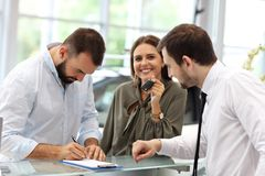 Confident young salesman explaining car features to the young attractive owners royalty free stock photo
