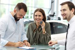 Confident young salesman explaining car features to the young attractive owners royalty free stock images